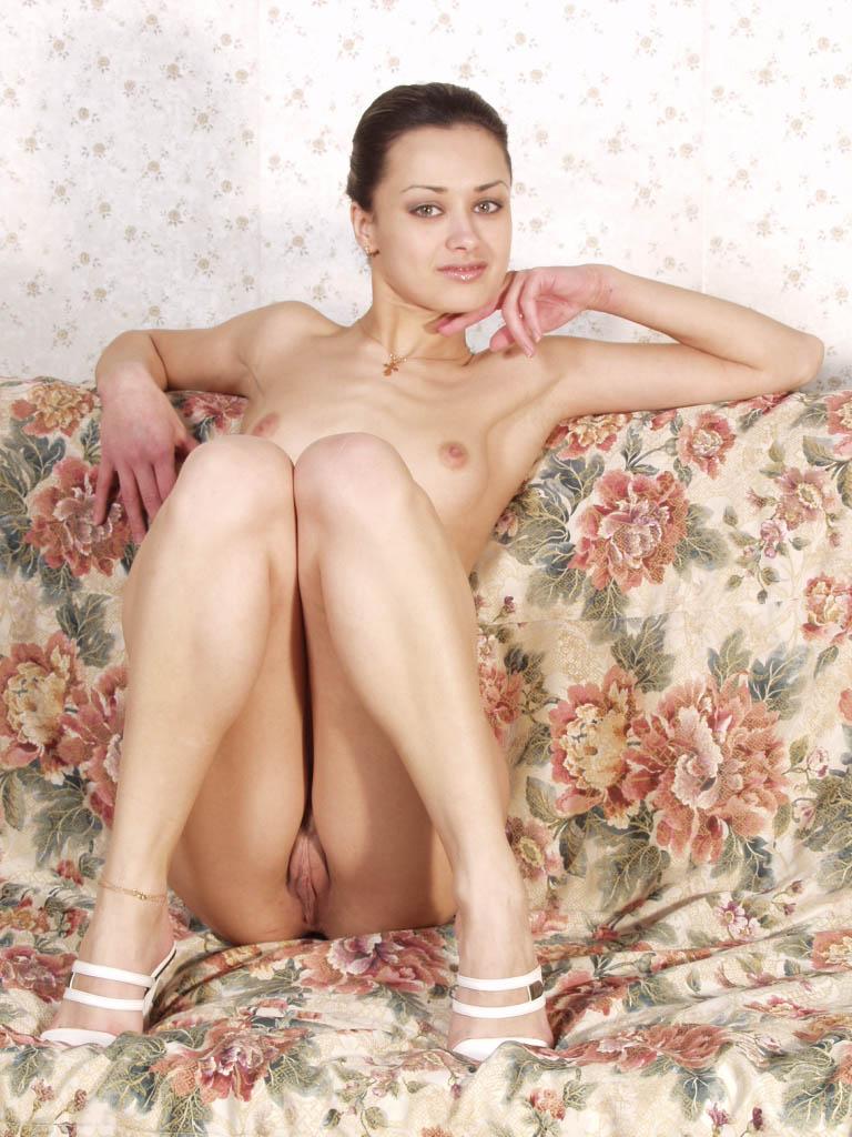 Голая брюнетка позирует на диване