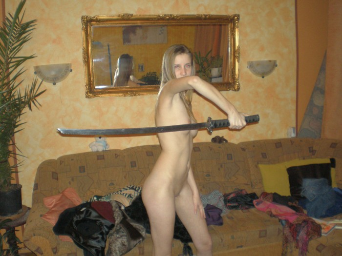 Sporty blonde with big boobs plays with sword