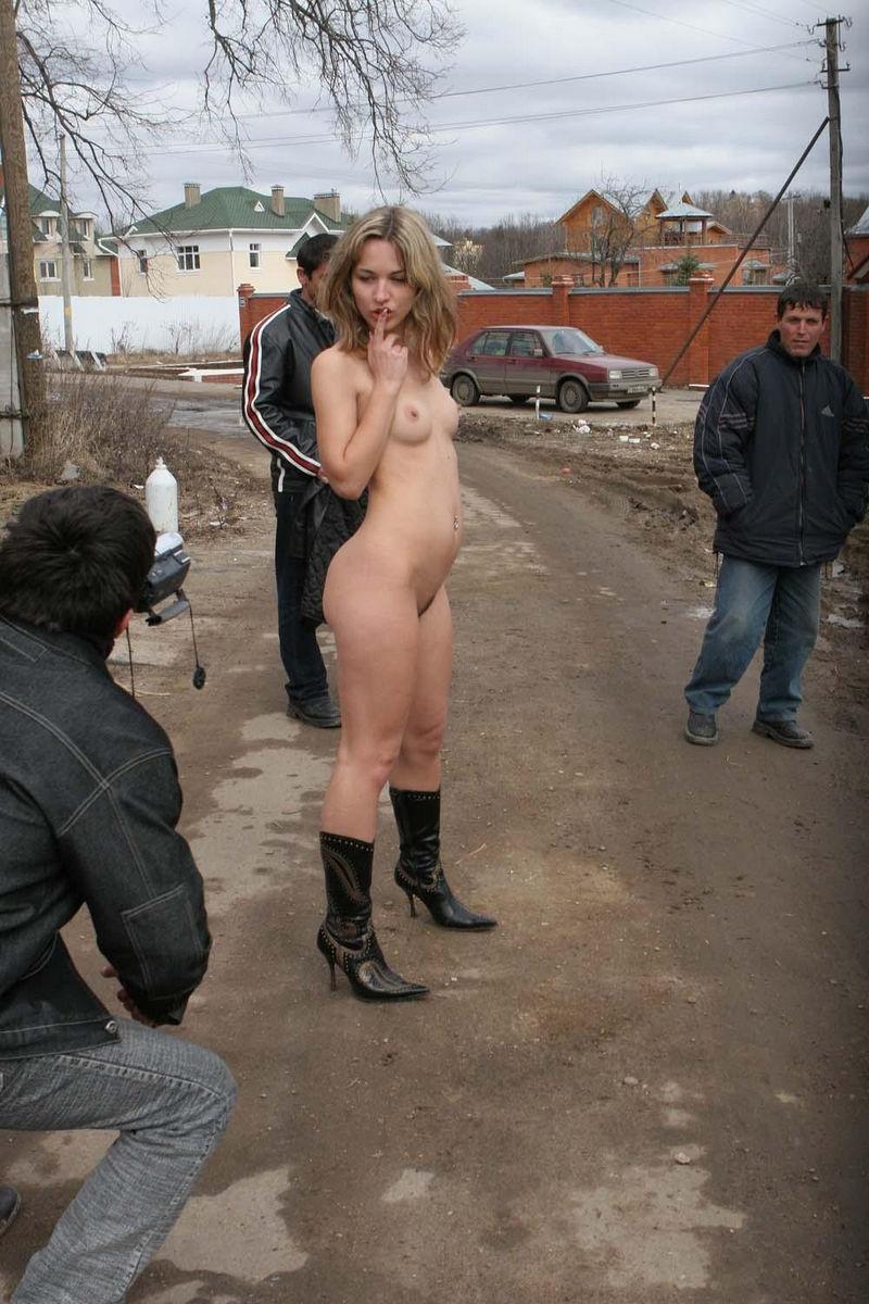 Голая девушка позирует на улице