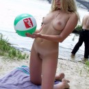 Blonde with big beautiful boobs plays with ball naked at the beach