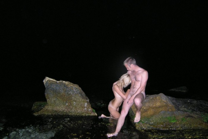 Young group posing naked at the beach at night