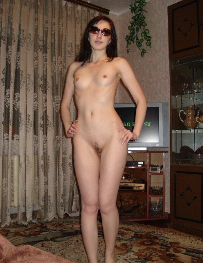Shy sporty russian girl in sunglasses posing at home