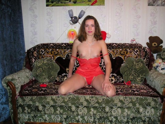 Naked woman shows her body in front of Christmas tree