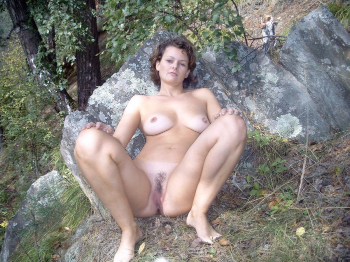 Juicy russian girl is taking a photo outside near a rock.JPG