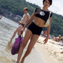 Short-haired brunette is undressing at public beach
