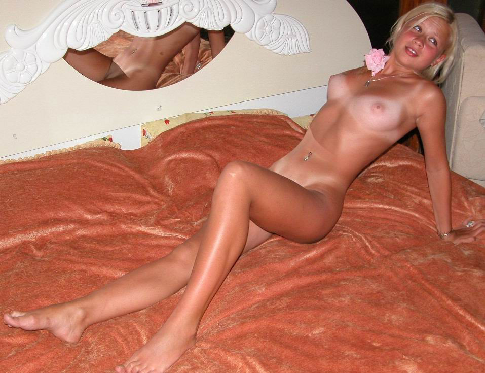 Tanned Blonde With Incredibly Enticing Legs Poses Naked On A Bed