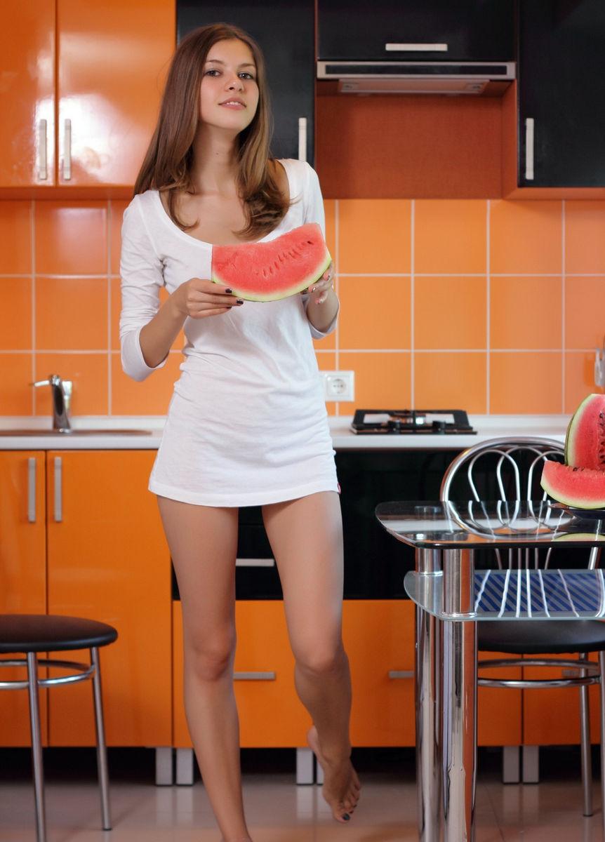 Голая милашка на кухне ест арбуз