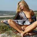 Blonde with big boobs posing naked at mountains