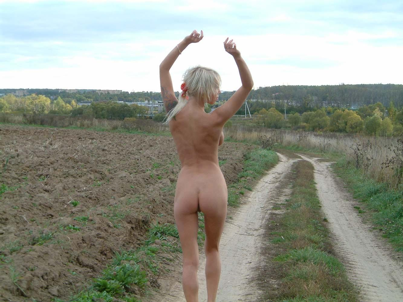 Short-haired blonde with big perky boobs walks outdoors ...