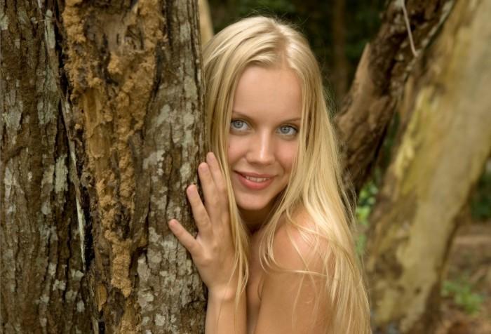 Худенькая блондинка позирует голой в лесу