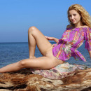 Curly russian blonde shows her shaved pussy on the beach
