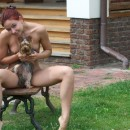 Russian girl with redhead and blue eyes posing with dog outdoors