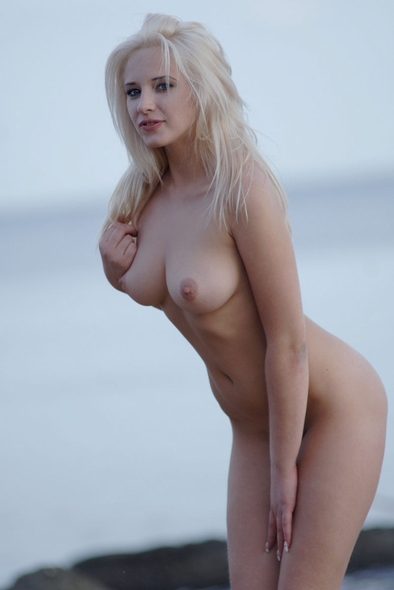 blonde with big tits chic photographed on the rocks by the