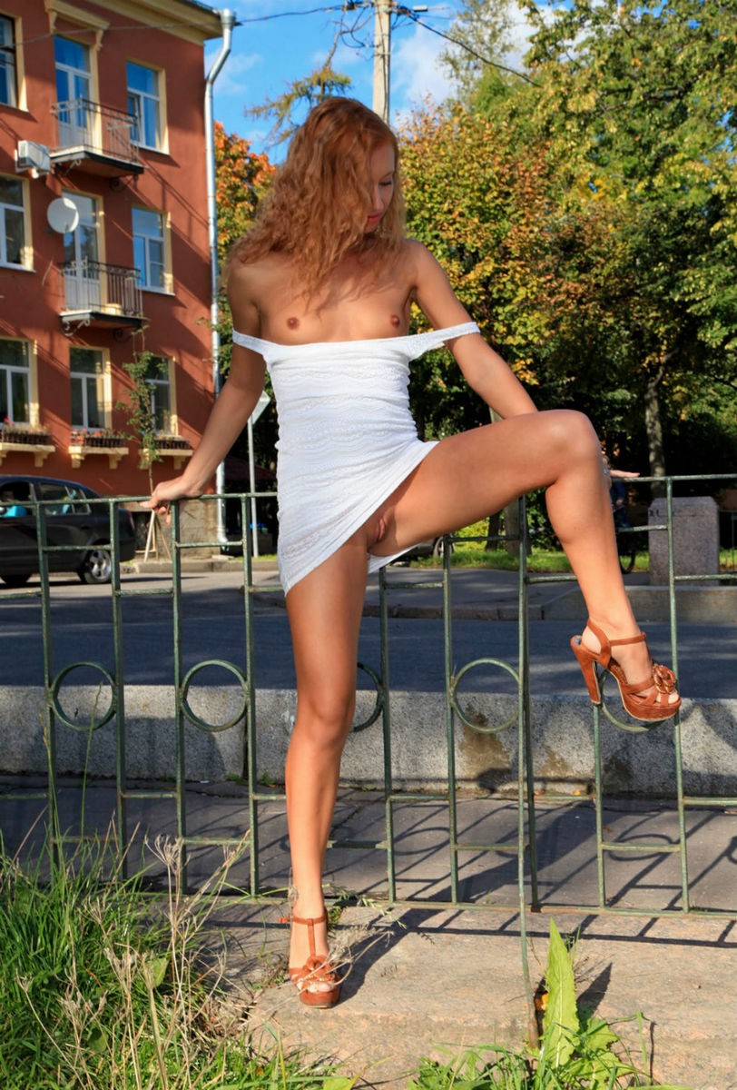 Curly Haired Girl In A Short Dress Is Walking Along The -2123