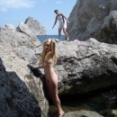 Lovely curly blonde with beautiful smile posing naked on the rocks at public place