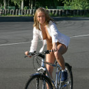 Naked blonde with awesome boobs ride bicycle at public park