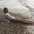 Young angel in very sexy transparent wet dress on the beach