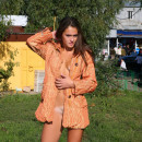 Lovely young girl with tan lines wears only coat to flash