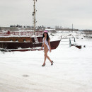 Skinny brunette posing naked at frozen pier