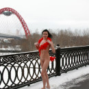 Sporty brunette teen with nice body walks naked at winter bridge