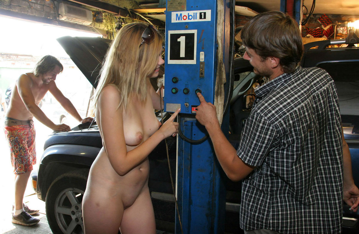 Blonde in denim skirt undressing in front of auto ...