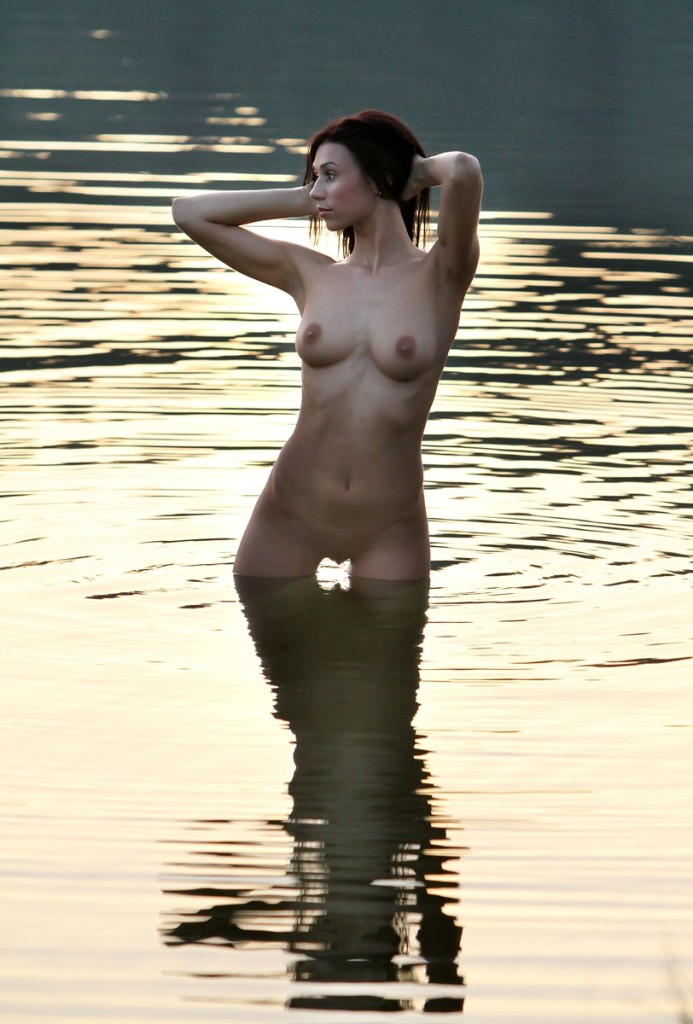 Gorgeous brunette posing naked in the lake in the early morning