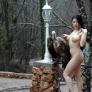 Naked brunette with long hair posing with a stuffed vulture on a bridge