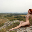 Naked red-haired woman on top of a sheer cliff