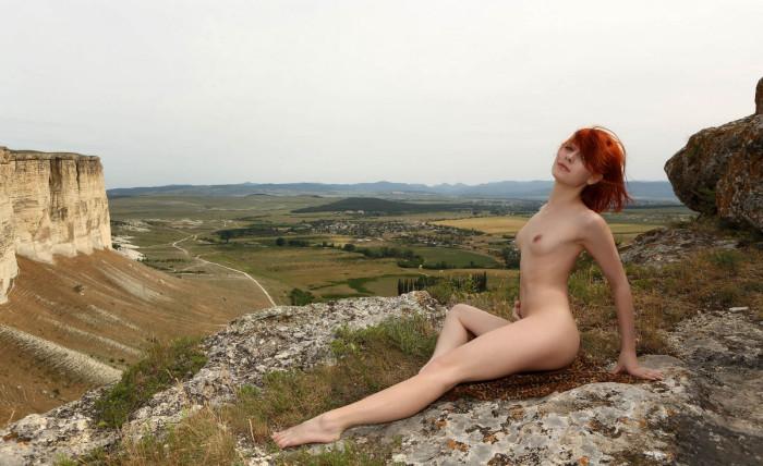 Naked red haired woman on top of a sheer cliff