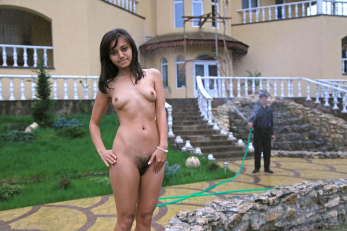 Dark skinned girl with hairy pussy posing under running out hose