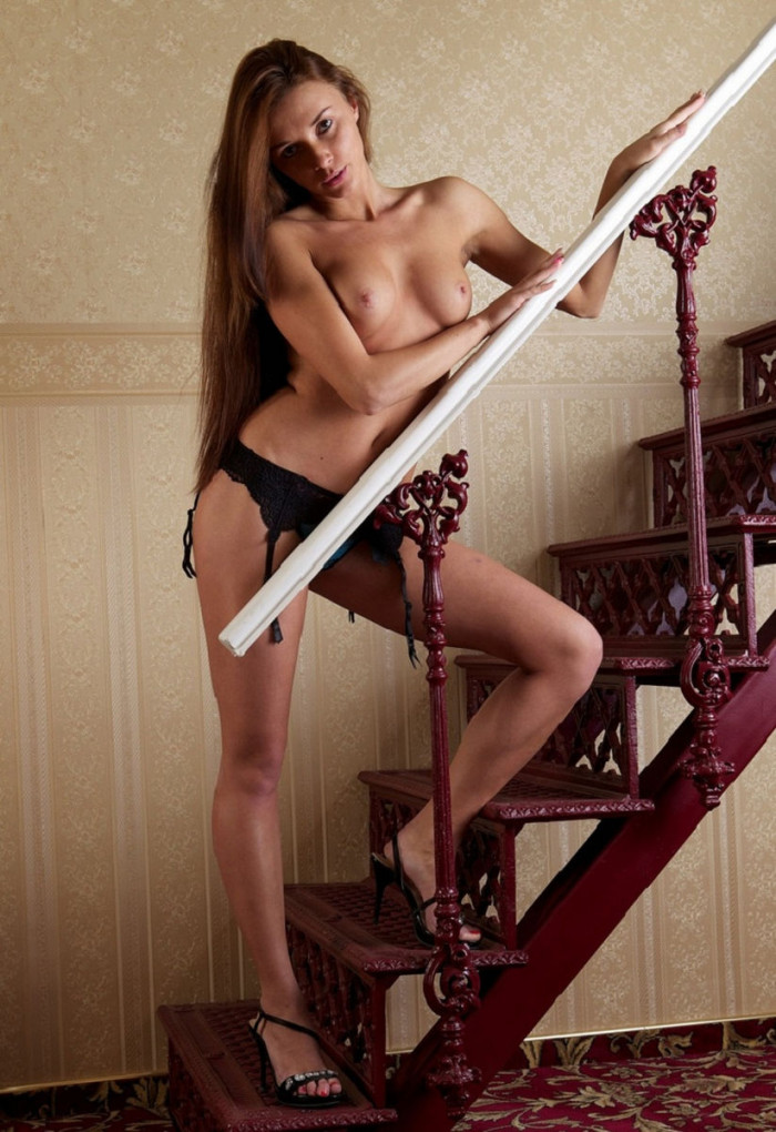 Girl with long hair takes off her sexy underwear on the stairs