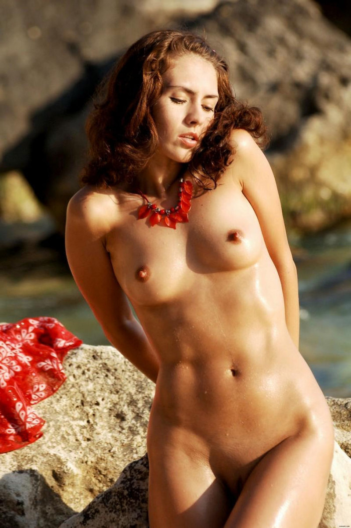 Lovely girl with erect nipples on a pebble beach