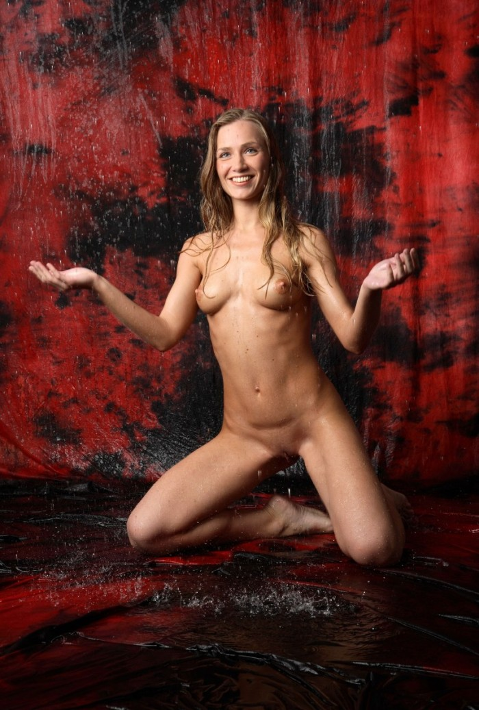 Tall smiling blonde under the rain in studio