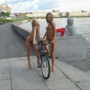 Two naked girl with a bicycle on the promenade road