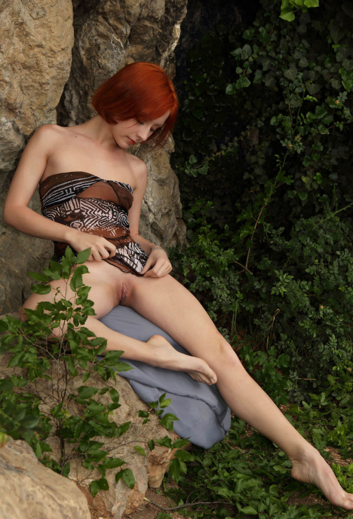 Red haired beauty with huge pussy under a rock