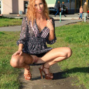 Redhead beauty shows her goods at public places