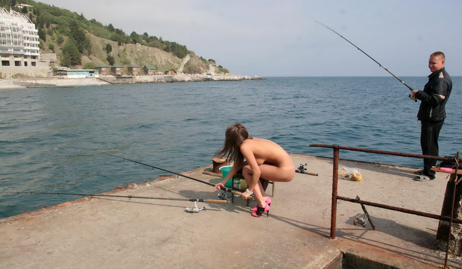 Young girl with a tattoo is fishing on the pier without ...