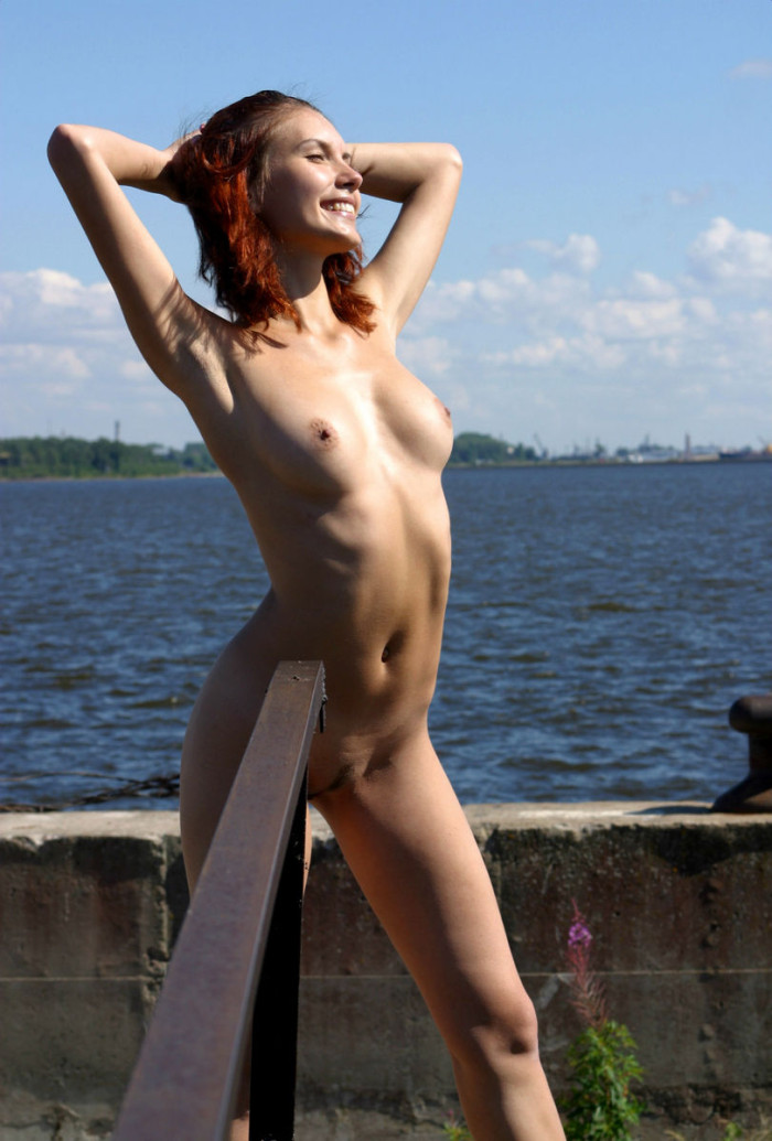 Busty red haired girl on the large pier