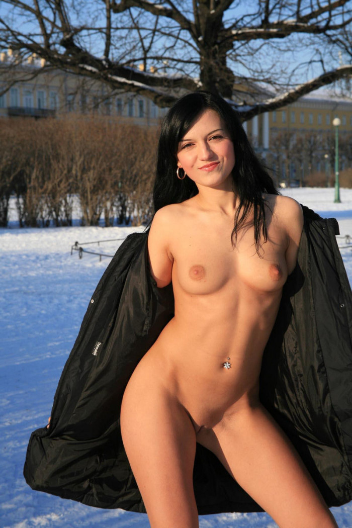 Naked brunette with piercing in the winter park