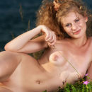 Curly beauty Katsia with piercing by the sea