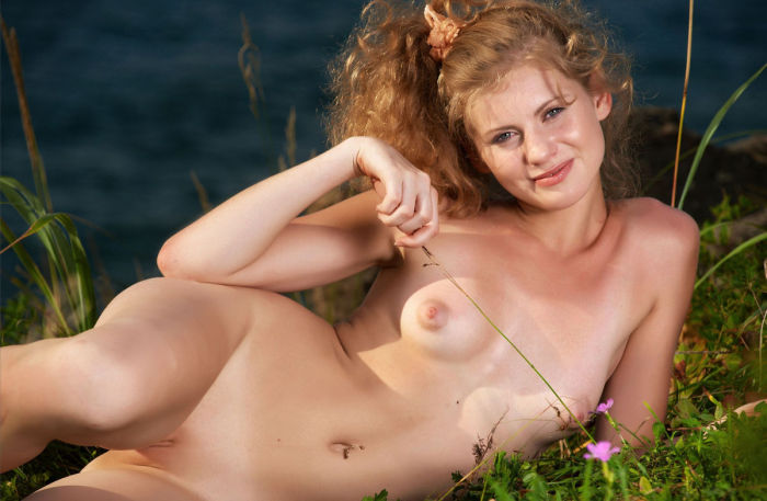 Red-haired doll posing bare on a public beach