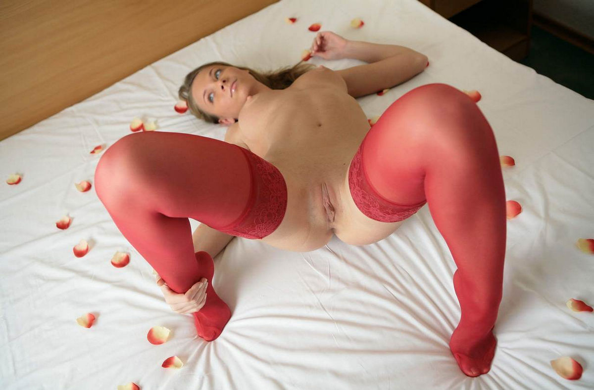 Lovely lady in crimson pantyhose on the bed with rose ...