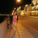 Russian girl takes off a pink dress on a night promenade