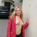 Blonde in stockings and pink coat posing in Moscow yards