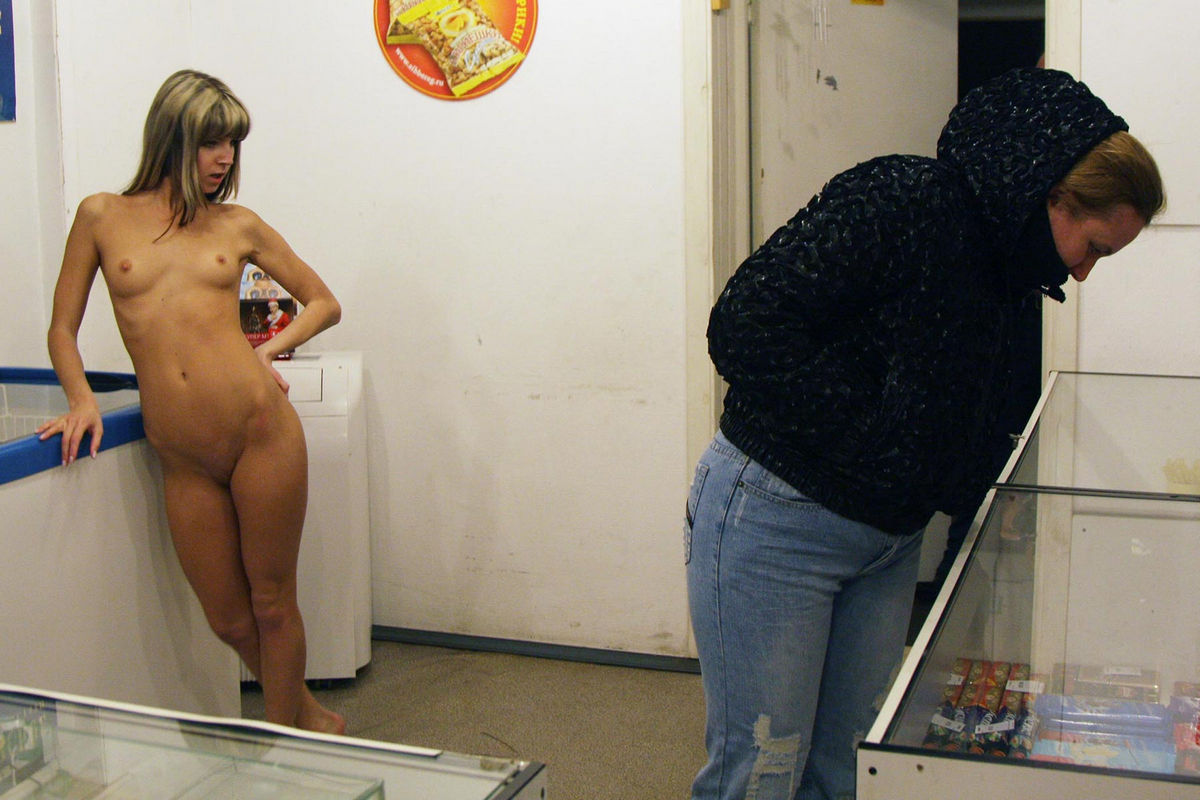 Slender young woman posing naked in a mini shop with ease ...