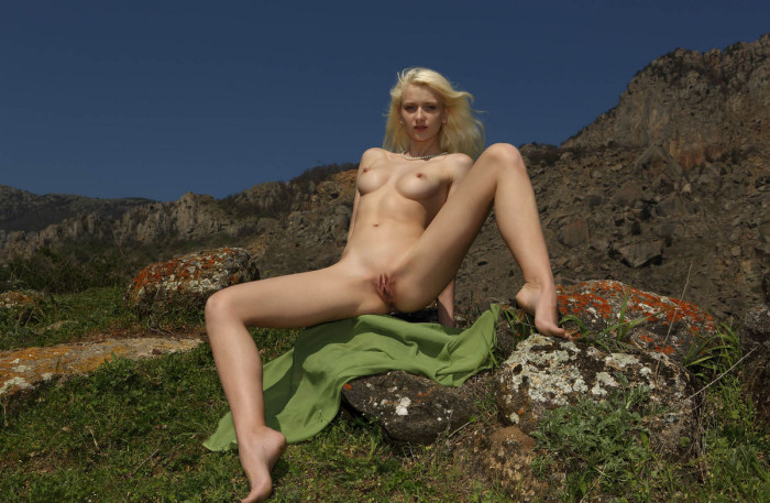 Naked girl on a public pebble beach