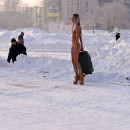 Tall slender girl with a suitcase in winter city
