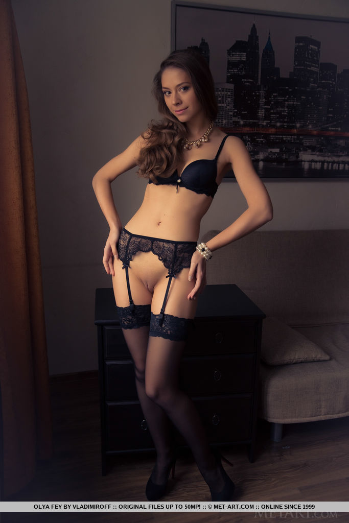 The gorgeous Olya Fey in matching black longerie, lace panty, thigh-high stocking with lace garter belt, and black stilettos