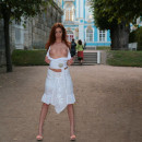 Redhead beauty in white dress flashes her goods at public park