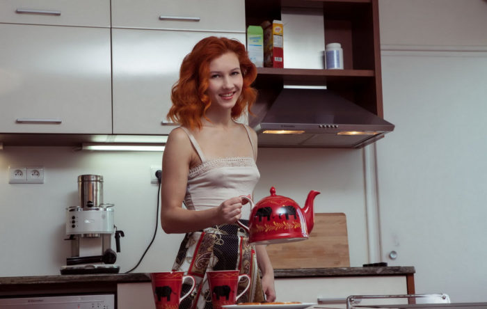 Fiery red-haired girl undressing in the kitchen